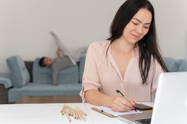 Donna del colpo medio che lavora con il computer portatile a casa
