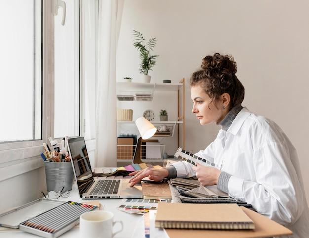 Donna del colpo medio che lavora con il computer portatile