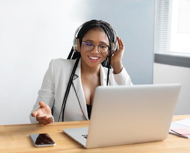 Medium shot woman working with laptop