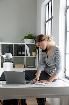 Средний снимок женщины, пишущей на ноутбуке