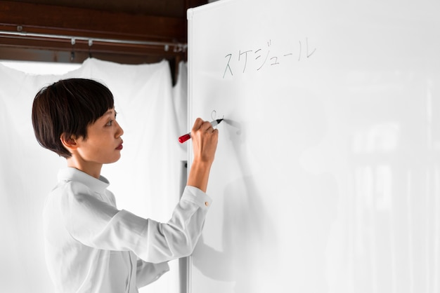 Medium shot woman writing on white board