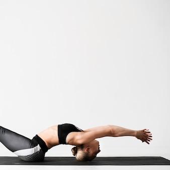 Medium shot woman on yoga mat