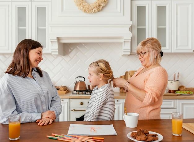ミディアムショットの女性とキッチンの女の子