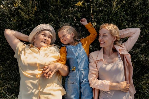ミディアムショットの女性と芝生の上の子供