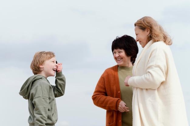 ミディアムショットの女性と屋外の子供