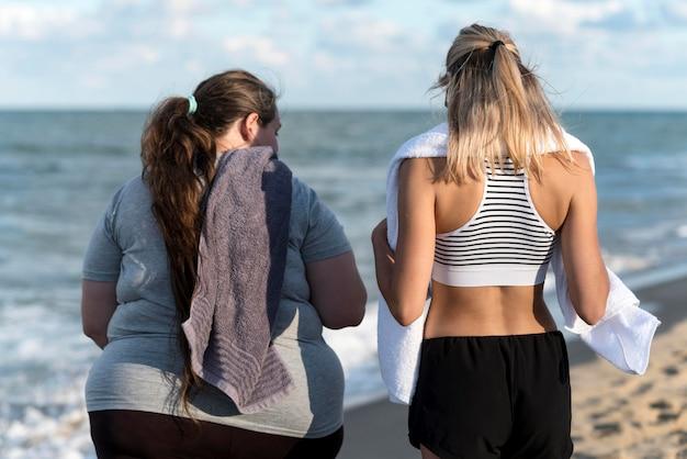 Donne del colpo medio alla vista posteriore della spiaggia