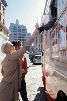 アイスクリームを買うミディアムショットの女性