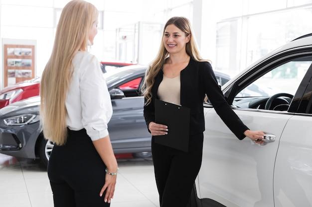 Medium shot of women at car dealership