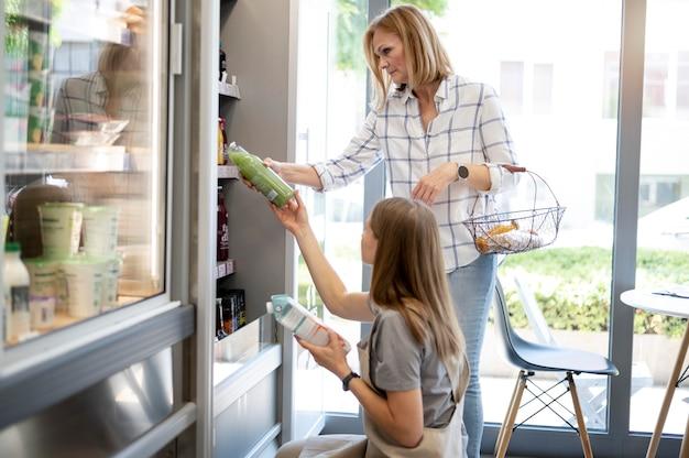 Donne di tiro medio che controllano i prodotti