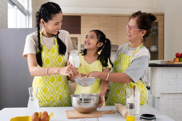 Medium shot women and girl cooking
