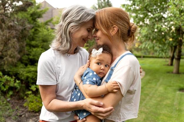 Medium shot women holding baby