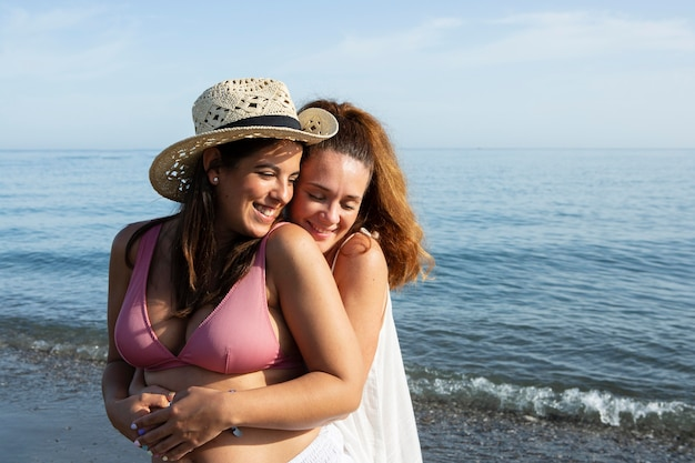 Medium shot women hugging at seaside