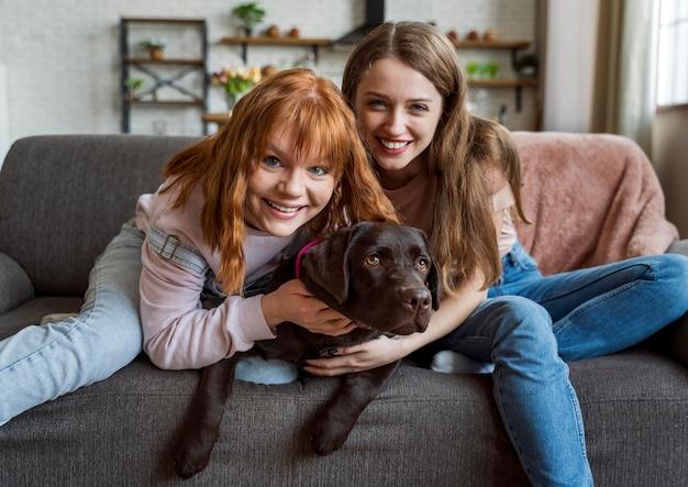 ソファに犬と一緒に横たわっているミディアムショットの女性