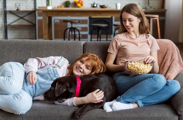 犬と一緒に横たわっているミディアムショットの女性