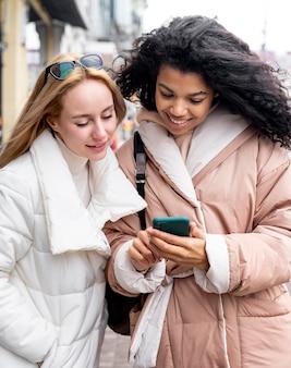 Donne del colpo medio che esaminano smartphone