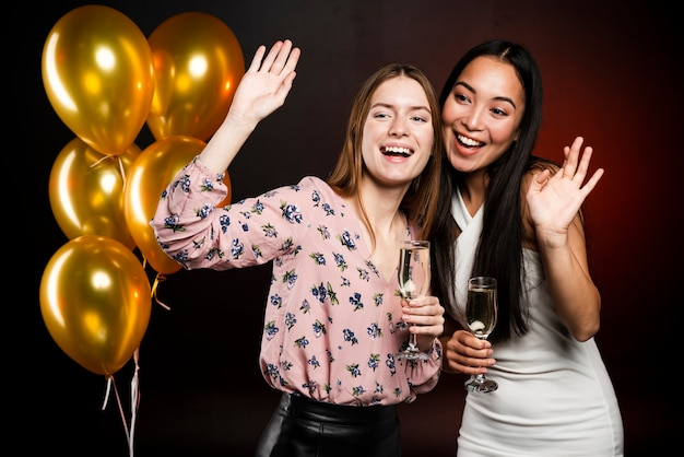 Medium shot of women at party posing with champagne