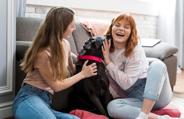 ミディアムショットの女性が犬をかわいがる