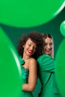 Donne a tiro medio in posa con palloncini verdi