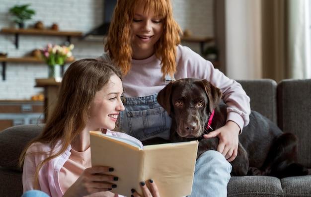 犬に読んでいるミディアムショットの女性