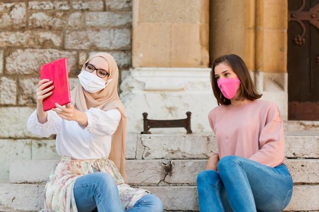 Medium shot women taking selfie outdoors