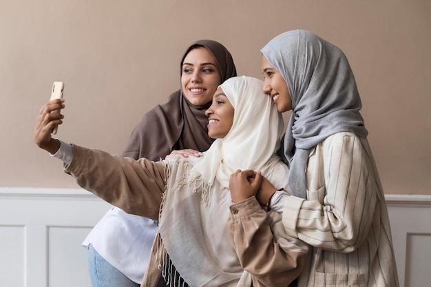 Donne a tiro medio che si fanno selfie