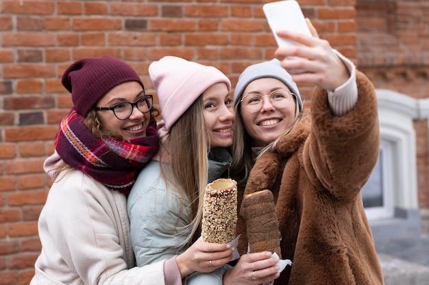 Medium shot women taking selfies