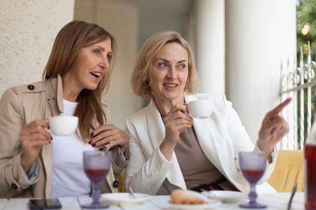 Medium shot women with coffee cups