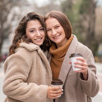 屋外でコーヒーを飲みながらミディアムショットの女性