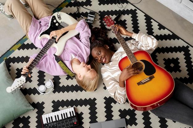 Donne di tiro medio con le chitarre sul pavimento