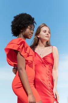 Donne di tiro medio con abiti rossi
