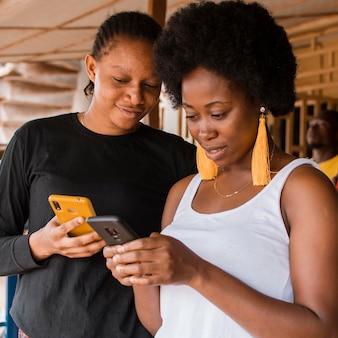 Женщины среднего кадра со смартфонами