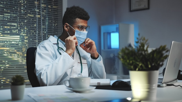 Medium shot of young african doctor showing how to wear medical mask by video call on computer