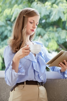 Medium shot of young blond woman standing at the balcony with a cup of coffee and tablet pc reading