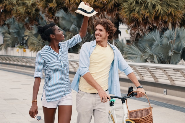 Medium shot of young couple walking with bicycle in the summer