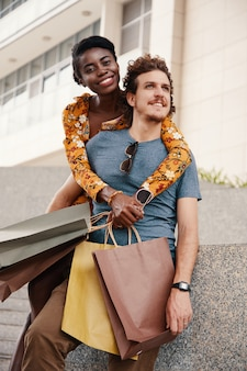 Medium shot of young crosscultural couple with shopping bags posing for a photo outdoors
