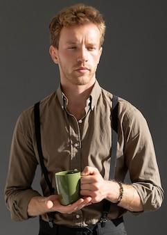 Средний снимок молодой мужской модели, держащей чашку кофе