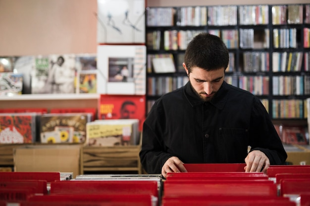 Medium shot of young man looking for vinyls in store