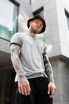 Medium shot young man with tattoos on arms
