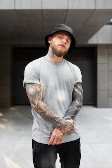 Medium shot young man with tattoos and hat