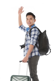 Medium shot of young tourist waving goodbye as he leaves for a journey