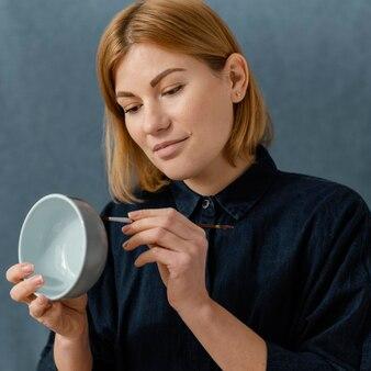 Ciotola della pittura della giovane donna del colpo medio