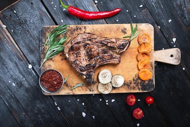 まな板の上に中型のステーキ、ジューシーな焼き肉。
