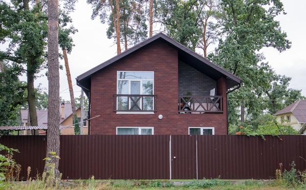 Средний небольшой коричневый частный дом с забором из профнастила в зеленом лесу летом. загородный дом на фоне леса. аренда коттеджей за городом на праздники.