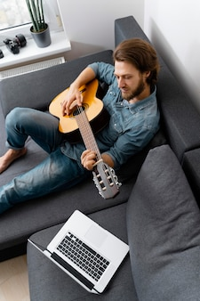 Mediums shot man playing guitar on couch