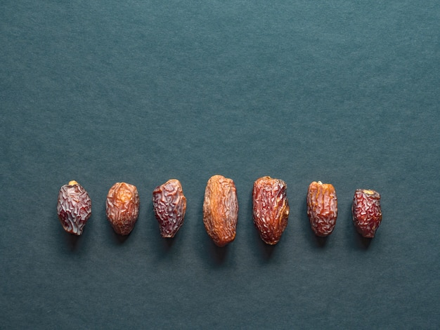 Medjool al-madina финики фрукты разложены на темном столе.
