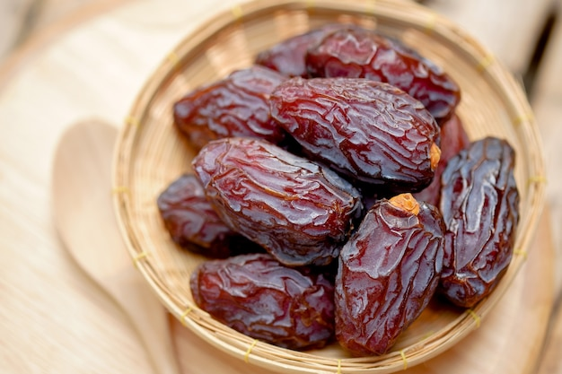 Medjool dates or dates fruit in wooden basket and spoon on table
