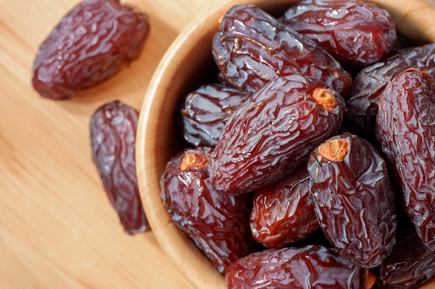Medjool dates in wooden bowl on table, top view. highly nutritious fruit increases breast milk for breastfeeding mothers.