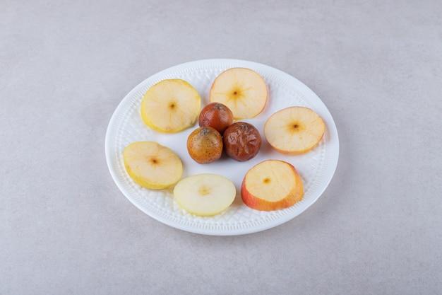 Мушмула и нарезанные яблоки на тарелке, на мраморе.