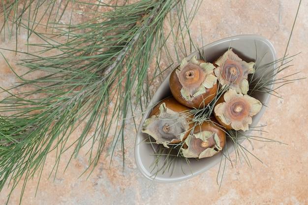 Плоды мушмулы в миске с травой на мраморном фоне.
