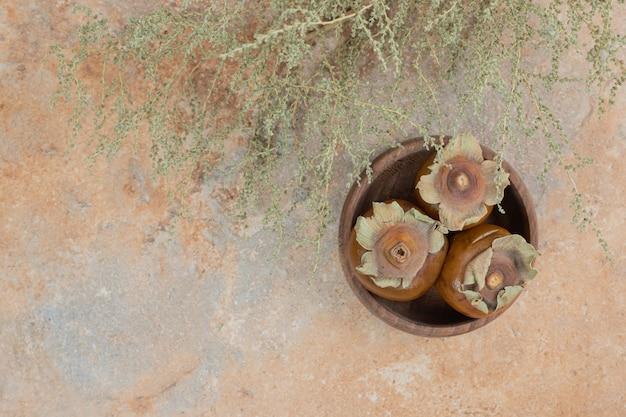 Плоды мушмулы в миске с травой на оранжевом фоне.